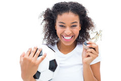 Pretty football player in white holding winners figurine and ball Royalty Free Stock Photos