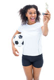 Pretty football player in white looking at winners figurine Royalty Free Stock Photo