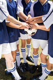 Pretty football players putting hands together Stock Images