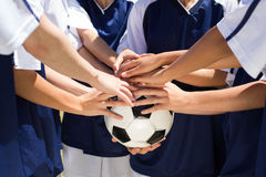 Pretty football players putting hands together Stock Photos