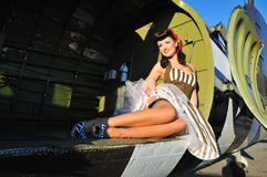 Pretty forties pinup sitting inside cargo aircraft Stock Photos