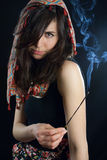 Pretty fortuneteller. Young fortuneteller in the smoke on black background Stock Photo