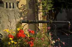 Pretty Fountain with Flowers, Alsace. Stone fountain, with big stoney faces, and pretty flowers, in Riquewihr, Alsace, France Stock Photography