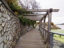 Pretty Framed Covered Walkway by the ocean. Framed wooden walkway / boardwalk on the seawall Stock Image