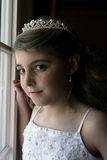 Pretty freckled girl standing at window stock image