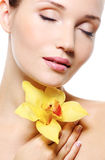 Pretty fresh clean female face with a flower. On white stock image