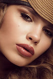 Pretty fresh girl, image of modern Twiggy in fashionable brown hat, with unusual eyelashes and curls. Royalty Free Stock Photography