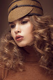 Pretty fresh girl, image of modern Twiggy in fashionable brown hat, with unusual eyelashes and curls. Royalty Free Stock Photo
