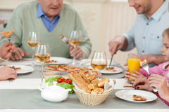 Pretty friendly family has a dinner together. There is no place like home. Cheerful grandparents are eating pizza with their children. They are sitting at the stock photography