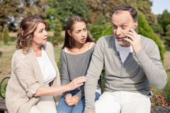 Pretty friendly family have heard some bad news. Cute old parents and their daughter are sitting in park. The men is talking on the phone. His eyes are wide open stock photo