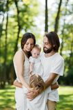 Pretty and friendly family is having rest in the park. Dad and mom are holding daughter in the arms and hugging their royalty free stock photo