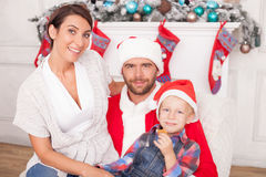 Pretty friendly family is making fun in New Year. Cheerful married couple and child are celebrating Christmas. The men is wearing costume of Santa Claus and Royalty Free Stock Images