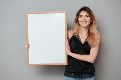Pretty friendly woman holding blank board and looking at camera. Portrait of a pretty friendly woman holding blank board and looking at camera  over grey Royalty Free Stock Photos
