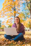 Pretty friendly woman sitting in an autumn park Royalty Free Stock Photos