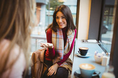Pretty friends chatting over coffee. In cafe Stock Photography