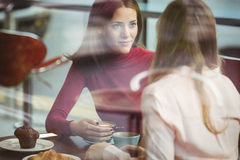 Pretty friends chatting over coffee. In cafe Royalty Free Stock Images