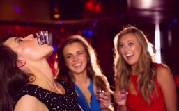 Pretty friends drinking shots together Stock Photo