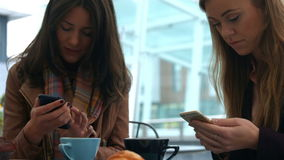 Pretty friends enjoying coffee in cafe using phones. In high quality format stock footage