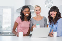 Pretty friends having coffee together with laptop. Smiling at camera in kitchen Stock Images
