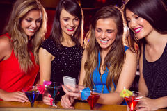Pretty friends looking at smartphone together Royalty Free Stock Photos