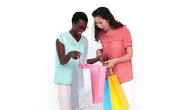 Pretty friends looking in their shopping bags. On white background stock video
