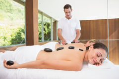 Pretty friends lying on massage tables getting hot stone massages Royalty Free Stock Image