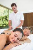 Pretty friends lying on massage tables getting hot stone massages Stock Image