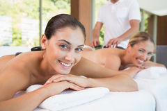 Pretty friends lying on massage tables with hot stones on their backs Royalty Free Stock Photography