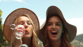 Pretty friends making bubbles stock video footage