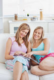 Pretty friends reading a magazine at home Stock Images