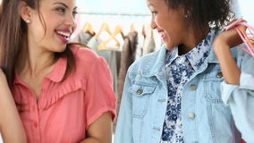 Pretty friends shopping together and smiling at camera. In a clothing store stock footage
