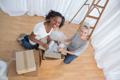 Pretty friends unpacking boxes in new home Stock Images