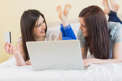 Pretty friends using a laptop to shop online lying on bed Stock Photo