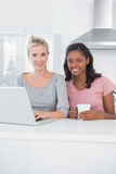 Pretty friends using laptop together and smiling at camera Stock Photo