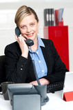 Pretty front desk lady attending clients call Stock Images
