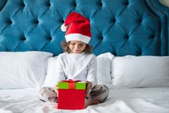 Pretty funny child girl with gifts in bed on Christmas morning. Happy funny child girl with gifts in bed on Christmas morning royalty free stock photo