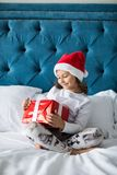 Pretty funny child girl with gifts in bed on Christmas morning. Happy funny child girl with gifts in bed on Christmas morning stock photography