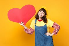 Pretty funny girl teenager in french beret and denim sundress holding big empty blank red heart isolated on yellow. Background in studio. People sincere stock images