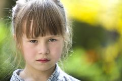 Pretty funny moody young child girl outdoor feeling angry and unsatisfied on blurred summer green background. Children tantrum stock photo