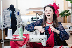 Pretty funny young pinup woman with sewing machine royalty free stock images