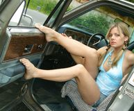 Pretty gal sitting in a truck. Young woman showing off her great legs Royalty Free Stock Image