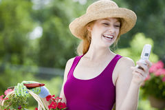 Pretty gardener with cell phone. Laughing woman gardener looking at her cell phone Royalty Free Stock Photos