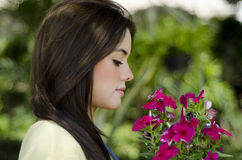 Pretty gardener with some flowers. Cute female gardener smelling some flowers at work Stock Photography
