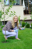 Pretty gardener woman with gardening tools. Outdoors planting apple tree Royalty Free Stock Image