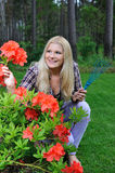 Pretty gardener woman with red flower bush Royalty Free Stock Image