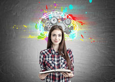 Pretty geek girl with a book and brain cogs. Portrait of a smiling beautiful teenage girl in a checkered shirt holding an open book and standing near a royalty free stock photo