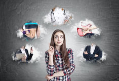 Pretty geek girl chosing her career. Portrait of a geek girl wearing a checkered shirt and standing with a finger pointing upwards near a blackboard with a Royalty Free Stock Images