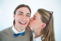 Pretty geeky hipster giving boyfriend kiss on the cheek Royalty Free Stock Photos