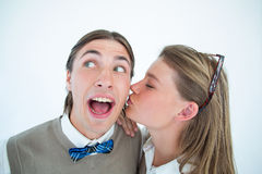 Pretty geeky hipster giving boyfriend kiss on the cheek Royalty Free Stock Images