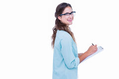 Pretty geeky hipster writing on notebook and smiling at camera Stock Images
